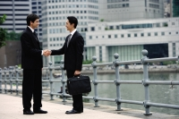 Two businessmen shaking hands, buildings in the background - Alex Mares-Manton