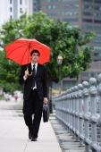 Businessman walking with briefcase and red umbrella - Alex Mares-Manton
