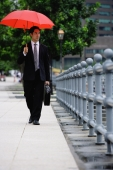 Businessman walking under red umbrella - Alex Mares-Manton