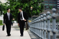 Two businessmen walking and talking - Alex Mares-Manton