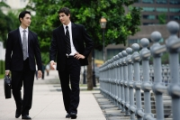 Two businessmen walking side by side, talking - Alex Mares-Manton