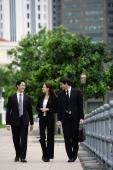 Business people walking side by side, talking - Alex Mares-Manton