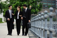 Business people walking in a row, talking - Alex Mares-Manton