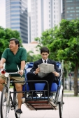 Businessman on trishaw, reading newspaper - Alex Microstock02