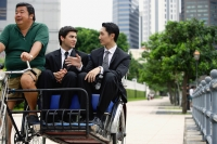 Two businessmen riding in trishaw - Alex Microstock02