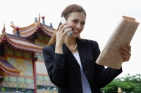 Businesswoman on mobile phone, looking at newspaper, Chinese temple in the background - Wang Leng