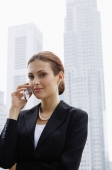 Businesswoman using mobile phone, buildings in the background - Alex Microstock02