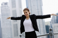 Businesswoman with arms outstretched, looking at camera, smiling - Wang Leng