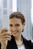 Businesswoman using mobile phone, photo messaging, looking at camera - Alex Microstock02