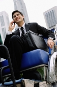 Businessman sitting in trishaw, using mobile phone - Alex Microstock02