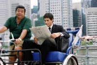 Businessman sitting in trishaw, reading newspaper - Alex Microstock02