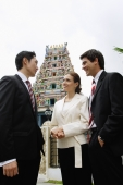 Two businessmen and one businesswoman standing, having a discussion, Hindu temple in the background - Wang Leng