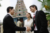 Two businessmen and one businesswoman in front of Hindu temple, shaking hands - Wang Leng