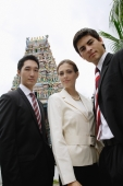 Two businessmen and one businesswoman in front of Hindu temple, looking at camera - Wang Leng