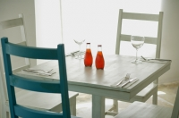 Table and chairs in restaurant with two bottled drinks on table - Alex Microstock02