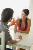 Couple toasting with drinks, sitting face to face - Alex Microstock02