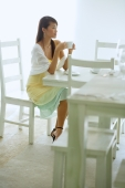Woman sitting at cafe table, holding cup - Alex Microstock02