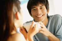 Couple holding cups, man smiling at camera - Alex Microstock02
