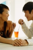 Couple sharing one drink, sitting face to face, holding hands - Alex Microstock02