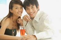 Couple with a drink between them, smiling at camera - Alex Microstock02