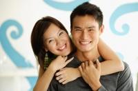 Woman with arm around man, both smiling at camera - Alex Microstock02