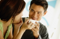Couple drinking from cups, looking at each other - Alex Microstock02
