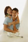 Woman embracing man from behind, both smiling at camera - Alex Microstock02