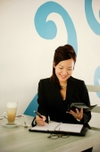 Businesswoman sitting at table, writing in personal organizer - Alex Microstock02