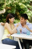 Couple sitting side by side, eating, woman feeding man - Alex Microstock02