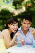 Couple sitting side by side, eating, smiling at camera - Alex Microstock02