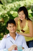 Couple smiling at camera, woman standing behind man, hand on shoulder - Alex Microstock02