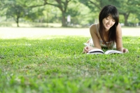 Young woman lying on grass in park, looking at magazine - Alex Microstock02