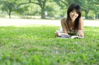 Young woman lying on grass in park, looking at camera - Alex Microstock02