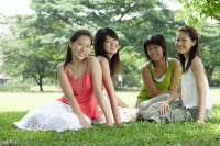 Young women sitting in park, smiling at camera - Alex Microstock02