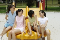 Young women sitting on slide in playground, talking - Alex Microstock02