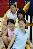 Young women sitting on slide in playground, smiling at camera - Alex Microstock02