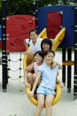 Young women sitting on slide, smiling at camera - Alex Microstock02