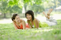 Two young women lying on grass, looking at camera - Alex Microstock02