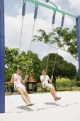 Young women on swings at playground - Alex Microstock02
