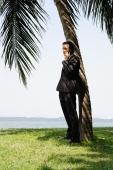 Businessman standing underneath tree, using mobile phone - Yukmin
