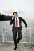 Businessman on boardwalk, using mobile phone - Yukmin
