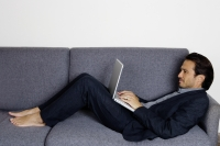 Businessman lying on sofa, using laptop - Yukmin