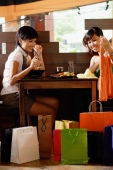 Young women in restaurant, looking at items from shopping bags - Alex Microstock02
