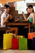 Two young women sitting at table in restaurant, surrounded by shopping bags, smiling at camera - Alex Microstock02