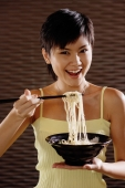 Young woman lifting noodles from bowl with chopsticks, smiling at camera - Alex Microstock02