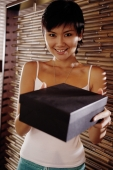 Young woman holding box, looking at camera - Alex Microstock02