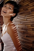Young woman next to bamboo screen, smiling - Alex Microstock02
