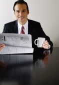 Businessman with newspaper and mug, smiling at camera - Yukmin