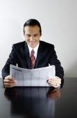 Businessman sitting at table reading newspaper, smiling - Yukmin