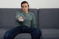 Man on sofa holding TV remote control - Yukmin